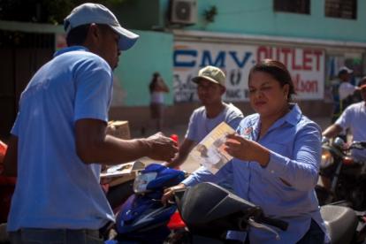 Un guía de Movilidad de San Andrés instruye a varios motociclistas que no llevan casco.