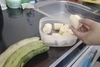 Una persona pela y corta un plátano verde para preparar patacones o tajadas fritas.