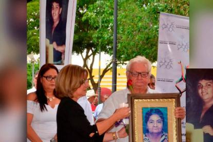 La ministra de Justicia, Margarita Cabello, le entrega una vela y una rosa roja a Luis Alfonso González, el padre de Gerzon González, el joven desaparecido en 1992 (en el recuadro).