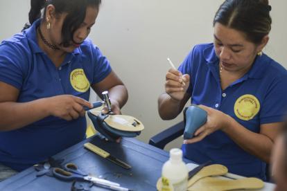 Mujeres emprendedoras trabajan en la elaboración de calzado femenino.