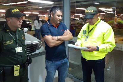Dos policías le leen los derechos a Carlos Mario Úsuga tras su captura.