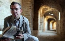 El autor español Santiago Posteguillo posa con su libro más reciente en el anfiteatro de Itálica, cerca de Sevilla (España).