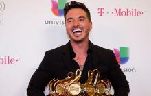 El artista colombiano J Balvin sostiene los cuatro trofeos que ganó en su categoría.