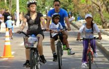 Niños y adultos se divierten en la ciclovía.