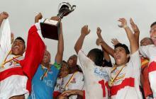 Los jugadores de la Selección Prejuvenil de Fútbol del Atlántico celebran en la tarima con el trofeo que los acredita como campeones.