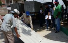 Trabajadores descargan tejas para asistir a afectados.