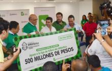Momento en el que el Alcalde le entrega el cheque simbólico a Moisés Díaz, Presidente de la Liga de Fútbol del Atlántico.