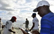 Antes de introducirse en alta mar, los pescadores consultan en un programa el estado del tiempo, mientras el resto alista sus elementos de trabajo.