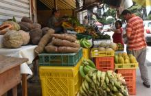 Reinaldo Rivero, de camiseta naranja, selecciona los alimentos que le indica una cliente de su negocio.