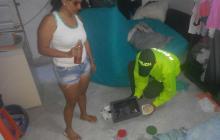 La capturada y un detective de la Sijín durante el allanamiento en Villa San Pedro.