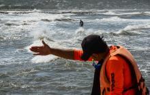 Un rescatista ordena a un bañista salir del agua debido a la intensidad del oleaje.