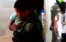 Un policía se lleva al menor luego de desatarlo.