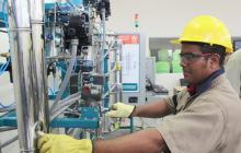 Un operario maniobra una máquina en una microempresa.