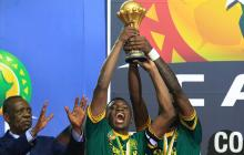 Moukandjo y Nkoulou levantan el trofeo de campeón.