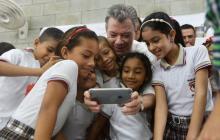 El mandatario de los colombianos mira un teléfono celular junto a unos niños.