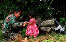 Una guerrillera de las Farc juega con una niña en una zona veredal.
