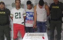 Los tres capturados, durante el proceso de reseña en la URI de la Fiscalía. Al frente, las balas y la droga que policías les encontraron.