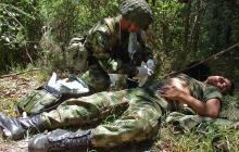 Un soldado atiende a un compañero herido en combate.