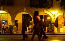Dos trabajadoras caminan por una calle, de noche.