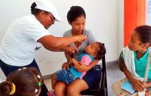 Enfermera aplica vacuna a niña en un centro de salud.