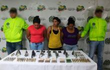 Las tres detenidas junto a las armas y el dinero incautado.