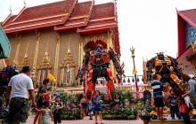 Turistas visitan las estatuas de los templos de Tailandia.