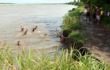 Jóvenes del sector se bañan en el río Magdalena, cerca del lugar donde fue hallado el cuerpo de la persona.