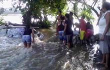 Un grupo de personas coloca sacos en el río Sinú.