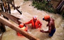Dos socorristas en el rescate de un hombre en medio de una creciente en zona rural de Lorica, Córdoba.