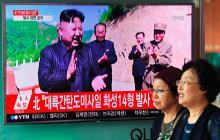 Dos mujeres caminan el 4 de julio frente a una pantalla de televisión en una estación de tren en Seúl, que muestra al líder norcoreano Kim Jong-Un celebrando el lanzamiento de prueba de un misil balístico intercontinental.