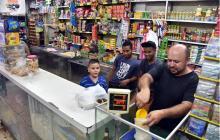 El tendero Nelson Suárez se prepara para atender a los clientes en su tienda, en el norte de Barranquilla.