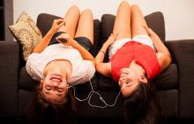 Dos jóvenes escuchan música acostadas en un sofá.