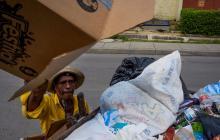 Un reciclador arroja en su carretilla una caja de cartón que acaba de recoger de la calle.