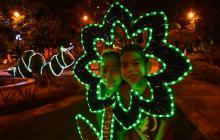Los niños posan en una de las flores que adornan el parque de los Fundadores.