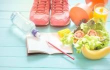 Zapatos deportivos, mancuerna  de ejercicio, bebidas, vegetales y un cuaderno. Elementos para cumplir propósitos de año nuevo.