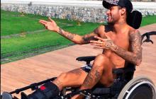 Neymar sentado en una silla de ruedas.