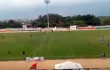 La cancha empieza a llenarse de directivos y padres de familia. Otros hombres saltan la valla de seguridad del estadio.