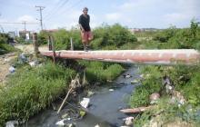 Un miembro de la comunidad atraviesa el arroyo por un puente improvisado.