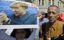 Una niña sostiene un póster de la canciller alemana Angela Merkel mientras un grupo de inmigrantes marchan por el centro de Budapest.