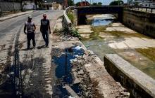 Dos hombres observan el punto desprotegido del arroyo, en la calle 29 con 23.