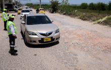 Unos vehículos circulan por un tramo vial de la carrera 38 en mal estado.