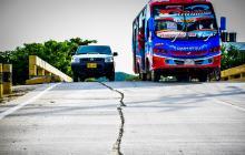 Un bus y una camioneta transitan por el puente, cerca de la grieta.
