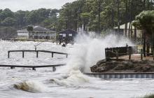 Las olas se estrellan contra un dique casero cuando la oleada comienza a subir la marea a medida que se acerca el huracán Michael a Florida.