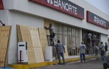 Dueños de varios establecimientos comerciales en Sinaloa protegen el frente de sus negocios ante la llegada de Willa.