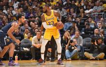 LeBron jugando ante la mirada de Kobe Bryant (d).