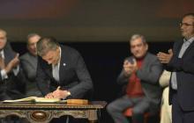 Juan Manuel Santos firma el acuerdo final en el teatro Colón, ante la mirada de Rodrigo Londoño.