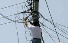 Un ciudadano manipula cables en un poste de luz.