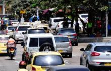 Atuomóviles y taxis transitan por una carretera.