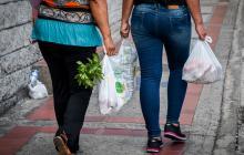 Dos mujeres cargan en unas bolsas plásticas de supermercado los alimentos que compraron en Barranquilla.