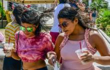 Un grupo de transeúntes intenta esquivar el polvo que a su paso levantan las fuertes brisas en Barranquilla.
